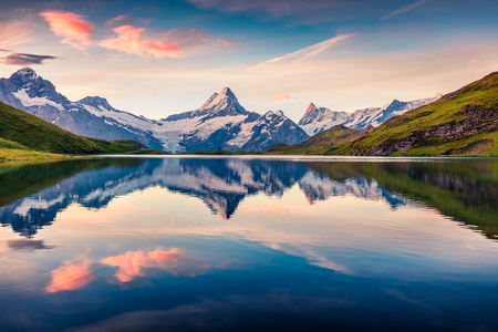 Foto de Colorful summer sunrise on Bachalpsee lake with Schreckhorn and Wetterhorn peaks on background. Picturesque morning scene in the Swiss Bernese Alps, Switzerland, Europe.  - Imagen libre de derechos