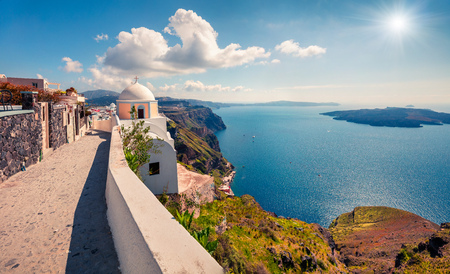 Cozy street of famous resort of Santorini - Fira. Sunny morning view of Thira, Greece. Traveling concept background.
