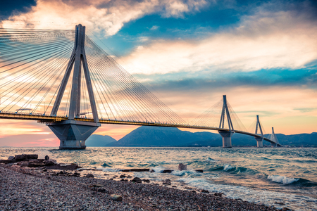 Dramatic evening scene with Rion-Antirion Bridge. Colorful spring scene of the Gulf of Corinth, Greece, Europe. Beauty of countryside concept background. Artistic style post processed photo.