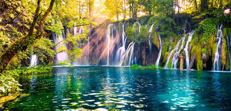 Foto de Last sunlight lights up the pure water waterfall on Plitvice National Park. Colorful spring panorama of green forest with blue lake. Great countryside view of Croatia, Europe. Beauty of nature concept background. - Imagen libre de derechos