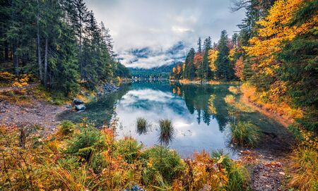 Photo pour Gloomy morning view of Eibsee lake. Amazing autumn scene of Bavarian Alps, Germany, Europe. Foggy mountain hills reflected in the calm surface of water ot pure lake. Beauty of nature concept background. - image libre de droit