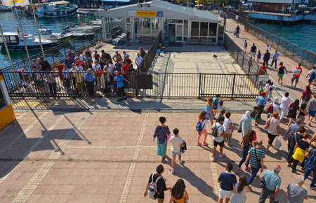 Foto per Burgazada, Turkey - September 18th 2019. Tourists disembark the ferry from Buyukada to Moda in Kadikoy, Istanbul, at the Burgazada ferry station in the Princes' Islands, also known as Adalar. More passengers await boarding behind the closed gates - Immagine Royalty Free