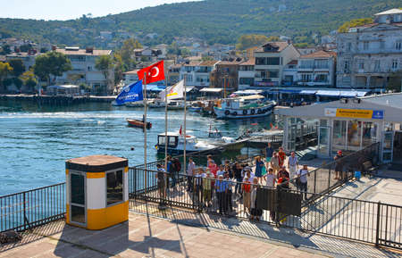Foto per Burgazada, Turkey - September 18th 2019. Tourists wait behind the closed gates to board the ferry from Buyukada to Moda in Kadikoy, Istanbul, at the Burgazada ferry station in the Princes' Islands, also known as Adalar. - Immagine Royalty Free