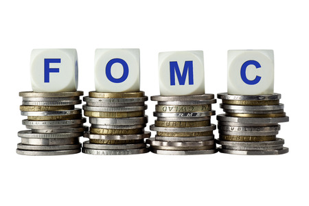 Stacks of coins with the letters FOMC isolated on white background
