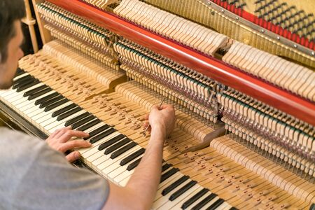 Photo for Piano tuning process. closeup of hand and tools of tuner working on grand piano. Detailed view of Upright Piano during a tuning. - Royalty Free Image