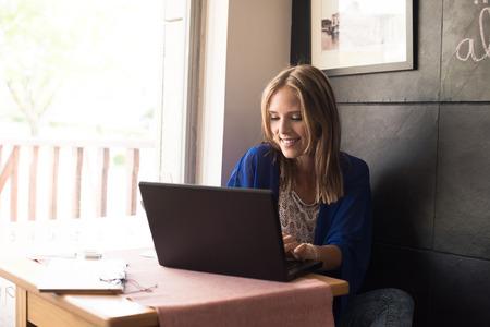 Photo pour Casual woman using laptop at coffee shop - image libre de droit