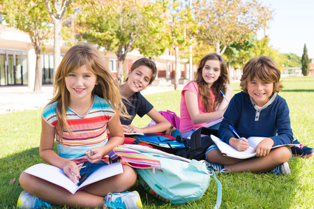 Photo pour Group of little students sitting on the grass at school - image libre de droit