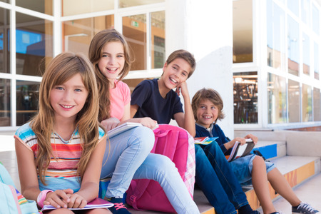 Photo for Group of school kids sitting on stairs - Royalty Free Image