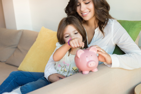 Photo pour Mother and daughter putting coins into piggy bank - image libre de droit