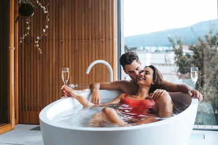 Photo pour Beautiful couple enjoying a relaxing bath with champagne - image libre de droit