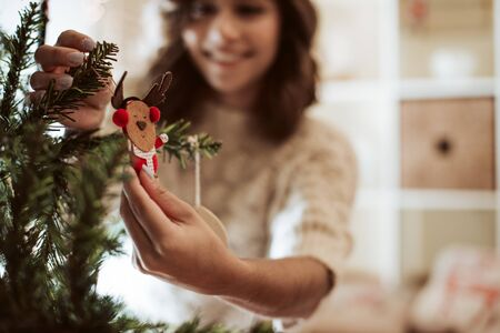 Foto de Woman decorating Christmas Tree at home - Winter Season - Imagen libre de derechos