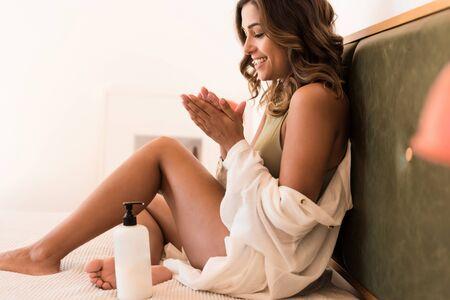 Foto de Latin woman applying body cream from a white container with copy space for branding - Imagen libre de derechos