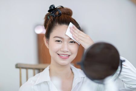 Photo pour Portrait of a Beauty young woman brunette cosmetics looking in the mirror using tissue with toner for cleaning make up with fresh healthy facial skin,feeling so fresh and happiness,Beauty and Cosmetic - image libre de droit