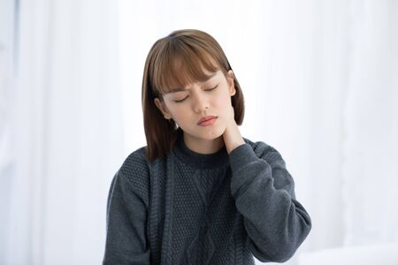 Photo pour young Asian woman sitting on bed has neck pain after wake up in the morning,Healthcare Concept - image libre de droit
