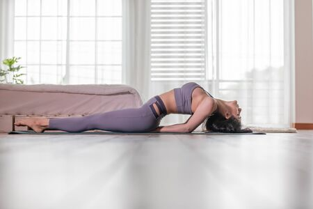 Beautiful Attractive Asian woman practice yoga Fish or yoga Matsyasana pose to meditation with yoga in bedroom,Recreation in holidays concept