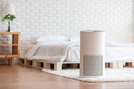 Photo pour Air purifier in cozy white bed room for filter and cleaning removing dust PM2.5 HEPA in home,for fresh air and healthy life,Air Pollution Concept - image libre de droit