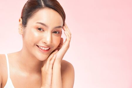 Photo pour Beautiful Young Asian Woman Holding Hands smile feeling so happy and cheerful with healthy Clean and Fresh skin,isolated on PINK background,Beauty Cosmetology and spa treatment Concept - image libre de droit