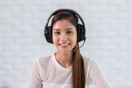 Photo pour Camera view of Happy young asian business woman wears headset talk to online video conference call with her business team during quarantine covid-19 self isolation at home,VDO Call Conference Concept - image libre de droit