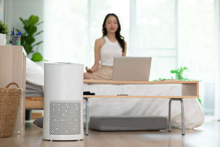 Photo pour Air purifier in cozy white Living room for filter and cleaning removing dust PM2.5 HEPA at home with woman exercise yoga in background,for fresh air and healthy life,Air Pollution Concept - image libre de droit