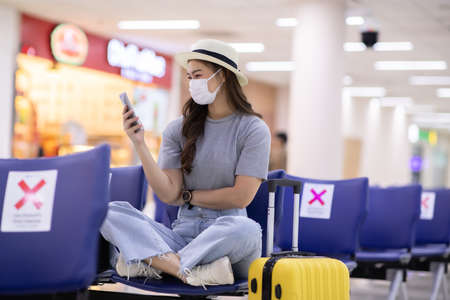 Photo pour Asian young woman traveller wearing face maks using mobile phone at airport Due Covid-19 flu virus pandemic and protection - image libre de droit