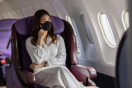 Photo pour Asian young woman wearing protective mask sitting near windows at first class on airplane during flight,Traveling and Business during COVID-19 virus pandemic concept - image libre de droit
