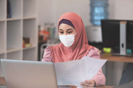 Photo pour New normal of Asian business Muslim or islam women wearing face protective mask in casual working with laptop and smile looking at camera at modern office or Co-Working Space,Business Startup Concept - image libre de droit