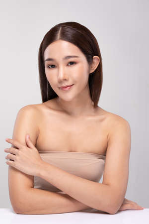 Photo pour Beautiful Young Asian Woman Looking While Touching Shoulder feeling so happy and cheerful with healthy Clean and Fresh skin,isolated on gray background,Beauty Cosmetology Concept - image libre de droit