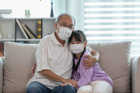 Photo pour Asian Elderly grandfather hug grandchild and wearing face mask on sofa at home protect virus infection - image libre de droit