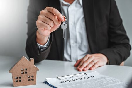 Photo pour Sale Agent giving house keys to woman customer and sign agreement documents for realty purchase. - image libre de droit
