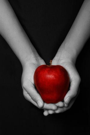 hands holding a red apple in black background