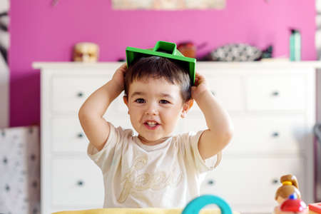 Photo pour Cute little boy playing in room at home with various toys - image libre de droit