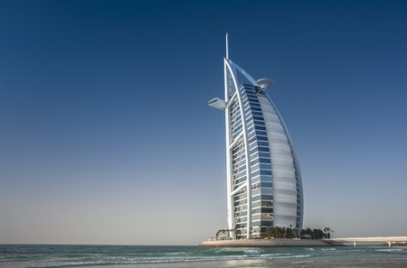 Photo pour Burj Al Arab, Tower of the Arabs, is a luxury hotel located in Dubai, United Arab Emirates. Burj Al Arab stands on an artificial island out from Jumeirah beach, and is connected to the mainland by a private curving bridge. - image libre de droit
