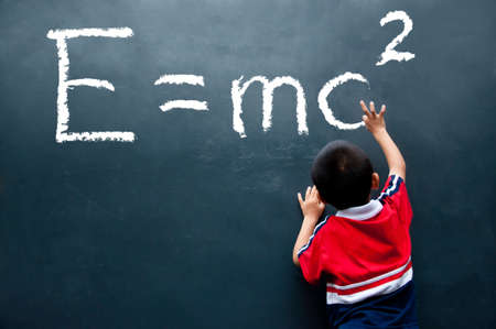boy drawing E=mc2 on the wall