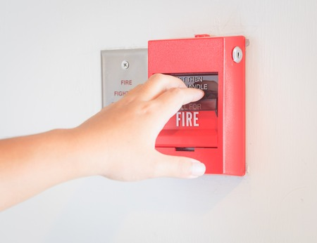 Photo for The hand  is pulling fire alarm on the wall - Royalty Free Image