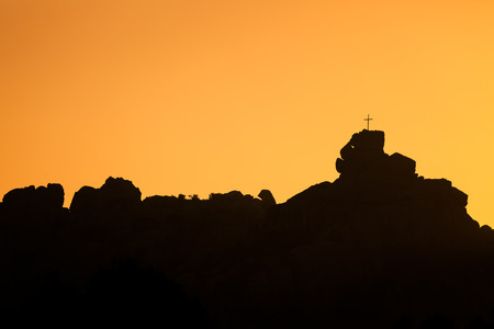 The cross on a rock at Mont de la Trinit? outside Bonifacio in the south of the island of Corsica silhouetted against an orange sunset