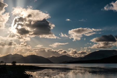 Late afternoon sun rays filtering through the clouds over Loch Linnhe in Scotland with mountains silhouetted in the distance