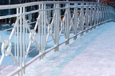 Metal fence of bridge in snow. Horizontally framed shot.