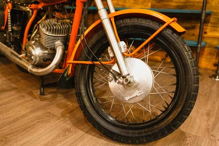 Vintage orange motorcycle detail. Spoke wheel and engine. Horizontally framed shot.