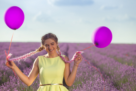 Portrait of a happy and joyful girl in yellow dress with a balloons in her hands. In the background, a lavender field and blue sky. Horizontally framed shot.