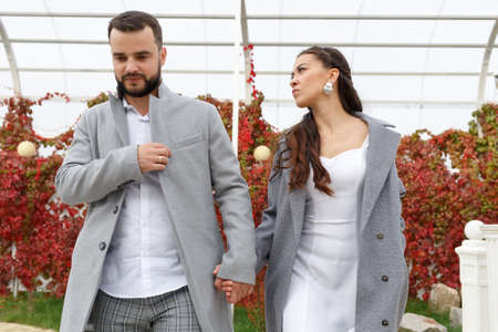 Photo pour Stylish couple in gray coats walking in the autumn park. Happy sensual wedding couple. Romantic moments of newlyweds. Horizontally framed shot. - image libre de droit