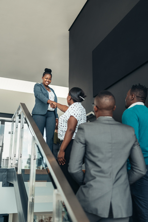 Smiling confident black businesswoman greeting and shaking hands with all african woman on stairsの写真素材