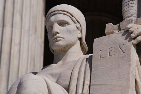 Statue outside the Supreme Court Building in Washington DC with a tablet that means law