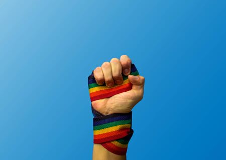 Foto de Hand punching up with lgbt flag, purple background - Imagen libre de derechos