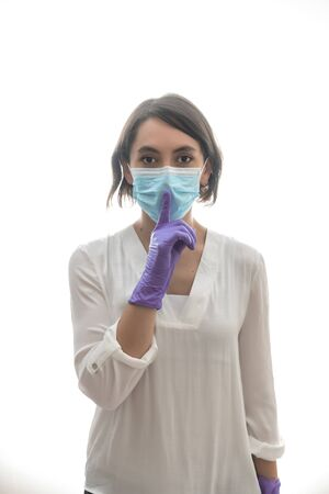 Woman with white shirt, purple gloves and mask, asking for silence for the covid19. With white background. Horizontal photo.