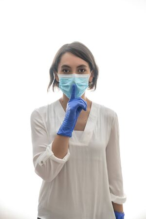 Woman with white shirt, blue gloves and mask, asking for silence for the covid19. With white background. Horizontal photo.