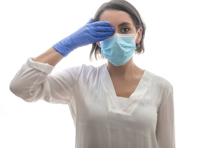 Woman in white shirt, blue gloves and mask, covering her eye with the covid19. With a white background. Horizontal photo.