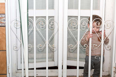 Foto de A year and a half old boy wanting to go out to his terrace in the quarantine, he has his fence closed. - Imagen libre de derechos