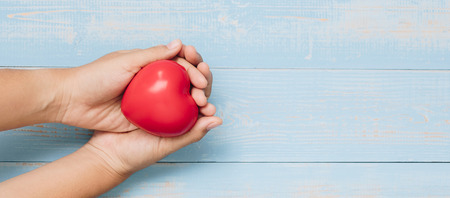 Foto de Top view hand holding red heart shape on blue pastel color wooden background. healthcare, organ donation, and insurance or Love and Valentine Day Concepts - Imagen libre de derechos