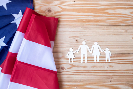 Photo pour People or Family paper shape with  flag of the United States of America on wooden background. USA holiday of Veterans, Memorial, Independence and Labor Day - image libre de droit