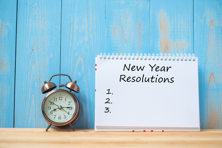 Foto de New years Resolutions text on notebook and retro alarm clock  on table and copy space. Goals, Mission and New Start Concept - Imagen libre de derechos